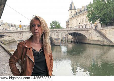 Portrait Of A Mature Blonde Woman In The City Of Paris. Saint Michel Bridge And Seine River Blurred