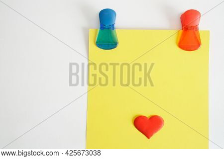 Colorful Magentic Pins Or Clips Hold A Yellow Piece Of Paper With A Red Heart On A Magnetic Board Or