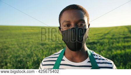 Portrait Of Positive Multiracial Male Farmer Wearing Protective Mask Staying In Planting Or At The F