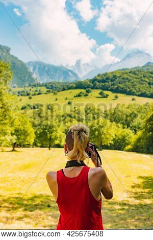 Young Girl From Behind With Red Shirt Taking Photograph Of The Mountainous Landscape Of The