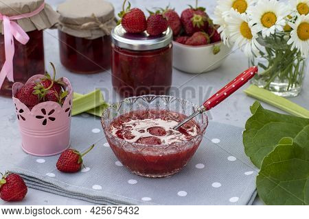 Homemade Strawberry And Rhubarb Jam In A Bowl And Jars On A Light Table In The Garden.