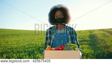 Portrait Of Positive Multiracial Female Farmer With Vegetables Staying In Planting Or At The Field A