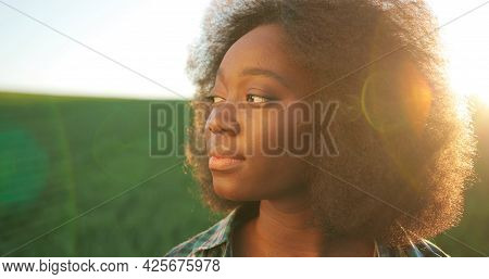 Portrait Of Positive Multiracial Female Farmer Staying In Planting Or At The Field And Smiling To Th