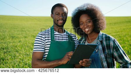 Male And Female Multiracial Engineers Using Digital Tablet While Inspecting Greenhouse Organic Farm
