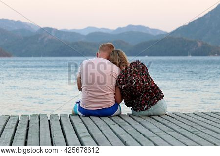Couple In Love Sit Huddled Together On Wooden Pier On Evening Sea And Misty Mountains Background. Be