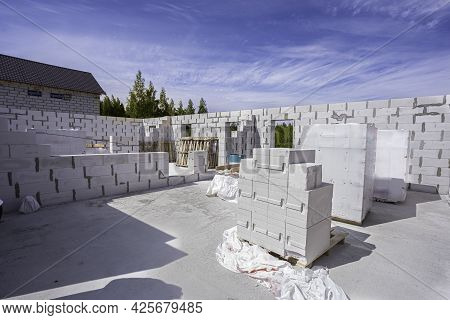 Home Construction. Raising The Walls With Aerated Concrete Blocks, Several Pallets Of Bricks