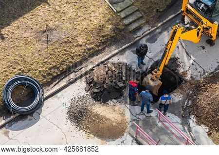 An Excavator Digs A Trench To Repair A Pipeline On A City Street.