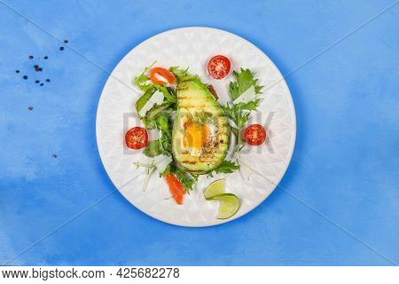 Original Fried Eggs Baked In Avocado, Served With Salad Leaves, Tomatoes And Parmesan. A Healthy, Nu