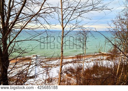 Nature Landscape With Dramatic Sky And Clouds, Lake With Ice, Shore With Snow And Dark Trees Without