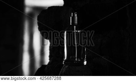 Perfume For Men On A Dark Background, A Glass Jar Of Perfume On A Background Of Bricks.