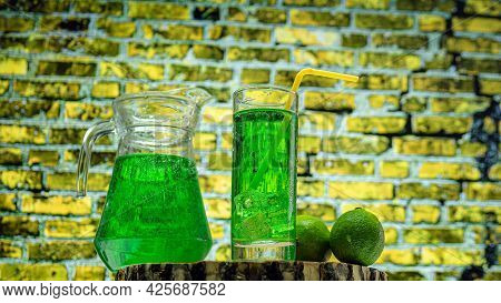 Fruit Green Drink In A Glass Against A Brick Wall Background, Green Lemonade In A Glass With Lime. S