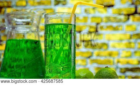 Green Lemonade In A Glass On A Yellow Brick Wall Background. Summer Fruit Drink With Ice. The Cockta