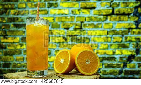 Orange Juice In A Glass With A Straw In A Transparent Glass Against The Background Of A Yellow Brick