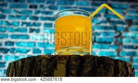 Orange Cocktail With A Straw On A Blue Brick Wall Background. Cooling Drink. Fruit Alcohol With Ice.