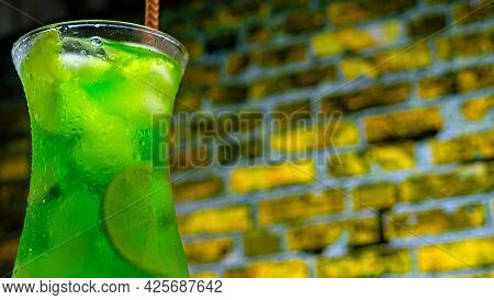 Green Octail In A Glass On A Brick Wall Background. Green Lemonade With Ice. Summer Fresh Drink In A