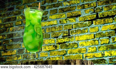 Close-up Juicy Cold Green Lemonade In A Glass Against The Background Of A Colored Brick Wall. The Co