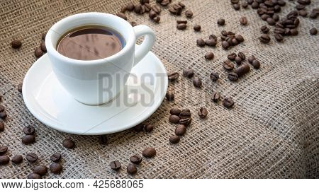 Cup Of Coffee With Sprinkle Coffee Beans On A Vintage Bag