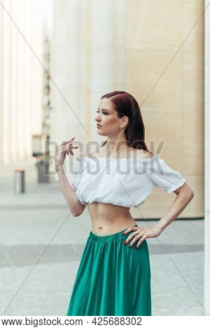 Portrait Of A Thirty Year Old Girl In Summer Clothes Against The Background Of A Modern Building.