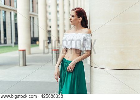 A Girl Of Thirty With Red Hair Next To A Fancy Building In The Summertime.