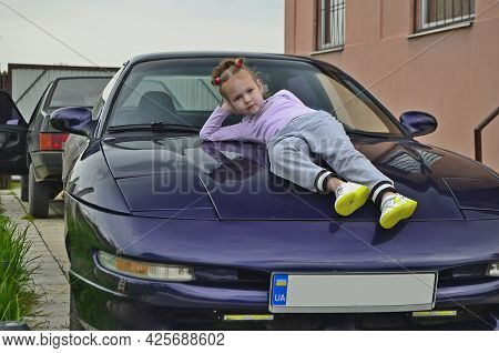 Little Girl Child On The Hood Of A Sports Car.