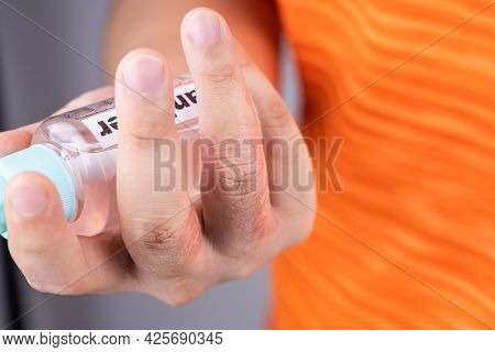 Dry Skin Finger With Bottle Of Hand Sanitizer. Sanitizer Causes Dryness With Frequent Use