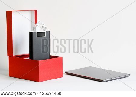External Battery - A Power Bank In A Red Box Next To A Discharged Smartphone, Tablet Or Phablet. The