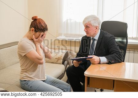 Caucasian Woman Crying At Psychotherapist Session. Male Psychiatrist Taking Notes On A Clipboard Dur