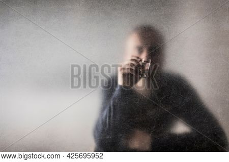 Man with a glass of vodka behind a dusty scratched glass. Alcoholism concept.