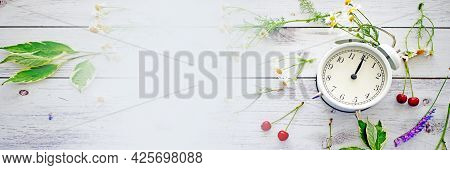 Summer Time Banner. White Alarm Clock Arrows Noon On A Wooden Table Around Wildflowers Fresh Berries