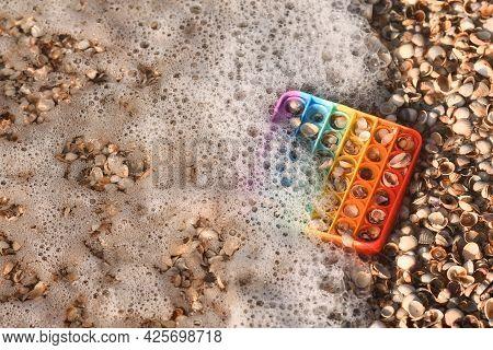 Pop It Is A Rubber Toy On Seashells In Foamed Seawater.