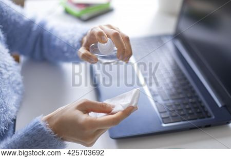 Young Woman Wiping Laptop Computer With Disinfectant Wipe While Working From Home