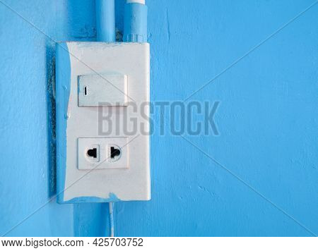 Old Power Sockets And Switches Are Mounted On Blue Cement Walls Inside The Building.
