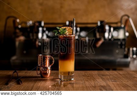Bumble Coffee From Americano And Orange Juice In Layers In Transparent Glass On Table