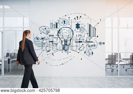 Business Woman Approaching To The Concrete Wall With Sketched Business Flowchart With Light Bulb To