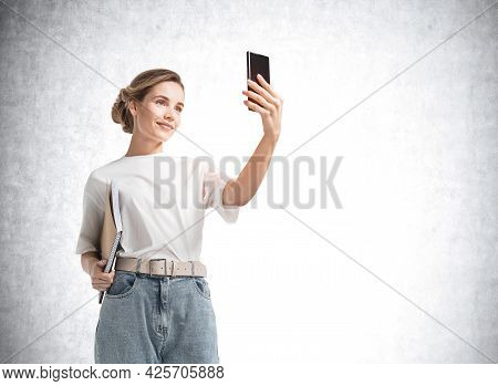 Attractive Young Woman In Casual Clothes Using Smartphone To Communicate With Business Colleagues Or