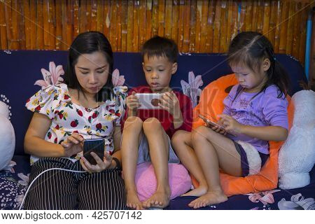 Happy Technology Addicted Asian Family Parents And Kids Use Phone Sit On Couch At Home, Mom With Chi