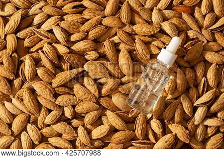 Essential Almond Oil And Serum Bottles Nuts Almonds With Shell On Beige Or Yellow Background, Top Vi