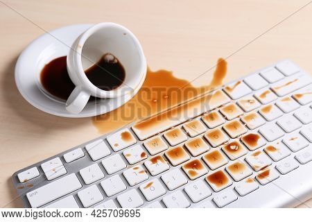 Cup Of Coffee Spilled Over Computer Keyboard On Wooden Table