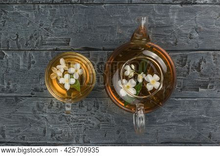A Glass Teapot And A Bowl With Lime Flowers On A Black Wooden Table. An Invigorating Drink That Is G