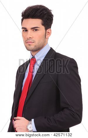 serious young business man is holding his glasses in his hand and looking at the camera, on white