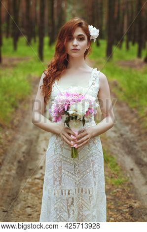 Outdoor Portrait Of Young Redhead Woman In Vintage Wedding Dress With Big Bouquet Of Pink Peonies. W