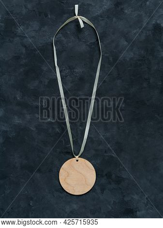 Blank Engraved Wooden Medal Mockup With White Ribbon And Copy Space On Dark Background Top View. Rou
