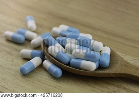Blue And White Capsules Pills In A Wooden Spoon On Wooden Background, Antimicrobial Capsule Pills, A
