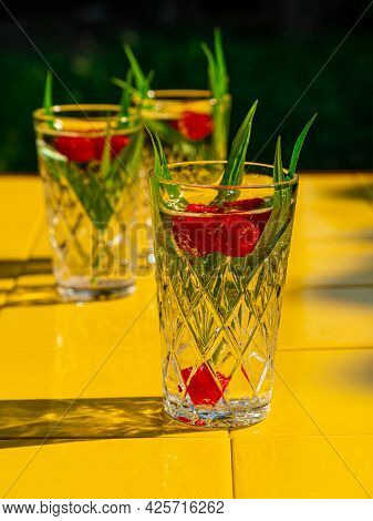 Refreshing Summer Drinks In Crystal Glasses Green Leaves Raspberry On Yellow Tile Background Sweet C