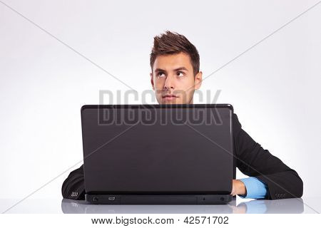 young business man sitting at the desk on his laptop and thinking