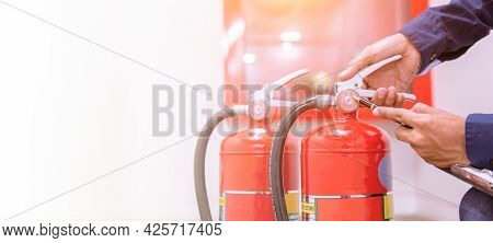 Firefighter Checking Pressure Gauge Level Of Fire Extinguisher Tank In The Building Concepts Of Prot