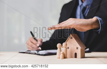 Insurance House, And Family Health Live Concept. The Insurance Agent Presents The ้hands Protection