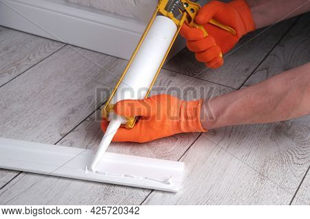 Master Applies Glue To  Skirting Board With  Glue Gun, Hands Close-up