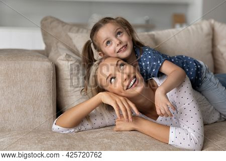 Close Up Smiling Dreamy Mother And Little Daughter Looking Up