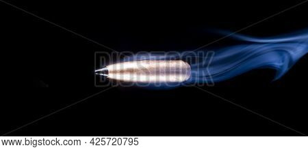 Copper Plated Bullet With Polymer Tip That Is On A Black Background With Smoke Behind